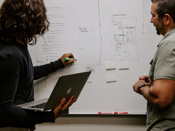 Two professionals collaborating on a whiteboard